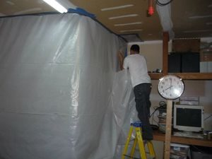 Water Damage Restoration Tech Sealing In Mold With A Vapor Barrier